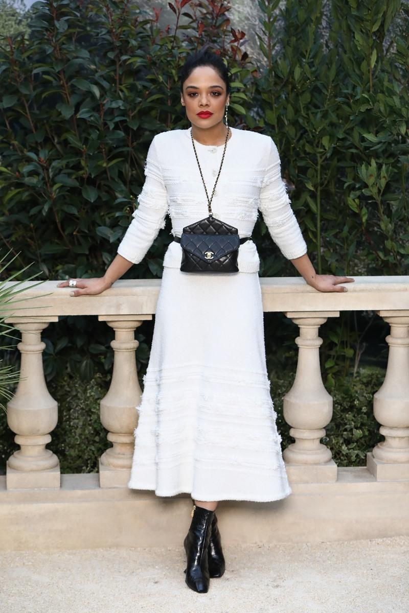 Tessa Thompson tham dự show diễn Haute Couture Xuân Hè 2019 của Chanel trong thiết kế đầm trắng với điểm nhấn là chiếc túi belt đặc sắc có quai xích luồn da vòng qua cổ. Đó cũng là món phụ kiện nổi bật trong BST Xuân Hè 2019 của Chanel.