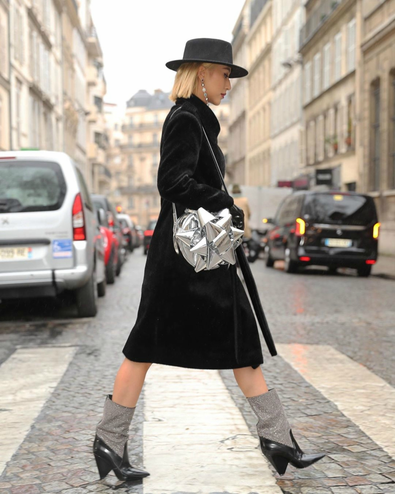 Trong show Christian Wijnants, Quỳnh Anh Shyn lại chọn tông đen cá tính từ nón, áo khoác đến giày để gây ấn tượng với giới mộ điệu quốc tế. Chi tiết ánh bạc từ hoa tai, túi xách và giày bốt cổ cao giúp tăng tính thời thượng cho diện mạo mà không làm mất đi vẻ bí ẩn