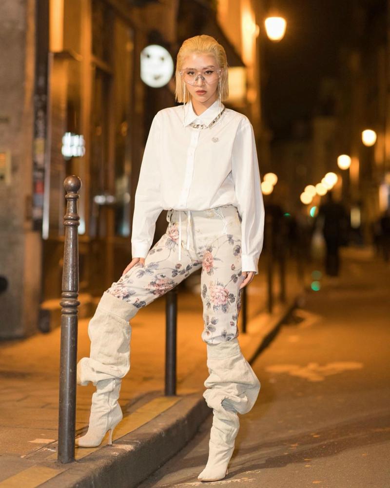 Tại show diễn của Kenzo, nàng hot girl Hà Nội diện áo sơ mi trắng, quần hoa ôm phối cùng đôi boots cổ cao dáng thụng