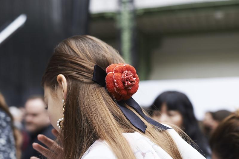 Kép tóc hình bông hoa trà màu đỏ với dải ruy-băng tạo điểm nhấn hoàn hảo cho mái tóc.