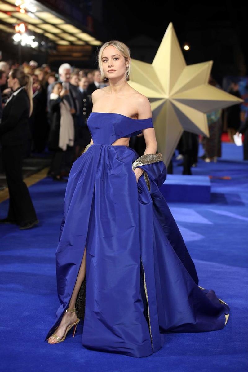 """Nữ diễn viên chính Brie Larson xuất hiện vô cùng lộng lẫy trong bộ đầm Haute Couture tông xanh biển dịu mát của nhà mốt Valentino. Thiết kế trễ vai kết hợp phần cut-out hai bên hông và tùng váy bồng bềnh tạo cho cô vẻ ngoài kiêu sa, gợi cảm nhưng vẫn khoe được những đường nét khỏe khoắn đúng chất của một nàng """"Đại úy Marvel""""."""