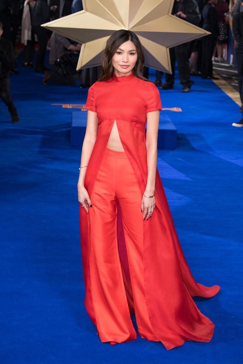 """Gemma Chan - nữ diễn viên thủ vai Tiến sĩ Minerva trong phim """"Đại úy Marvel"""" cũng có mặt trên thảm đỏ sự kiện lần này. Sau khi bị đánh giá xuống phong độ trong lần xuất hiện tại Oscar 2019, Gemma Chan đã trở lại hình tượng góc cạnh, cá tính trong sự kiện lần này. Cô lựa chọn bộ trang phục tông màu đỏ rực với quần ống suông oversized và áo vạt dài có khoảng xẻ khoe vòng eo thon gọn."""
