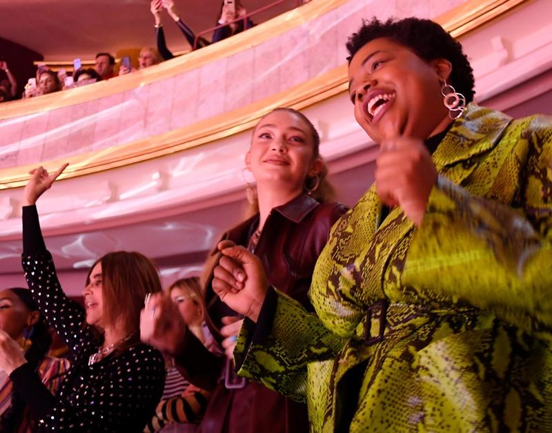 Gigi Hadid không thể ngồi yên với sự sôi động mà sàn diễn Tommy Now mang đến. Cô đứng cạnh bà Carine Roitfeld (cựu tổng biên tập Vogue Paris - bên trái).